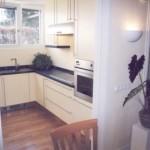 Küche in U-Form gelb lackiert mit schwarzer Steinplatte